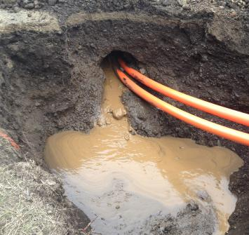 two hoses going into a ground, doing directional drilling